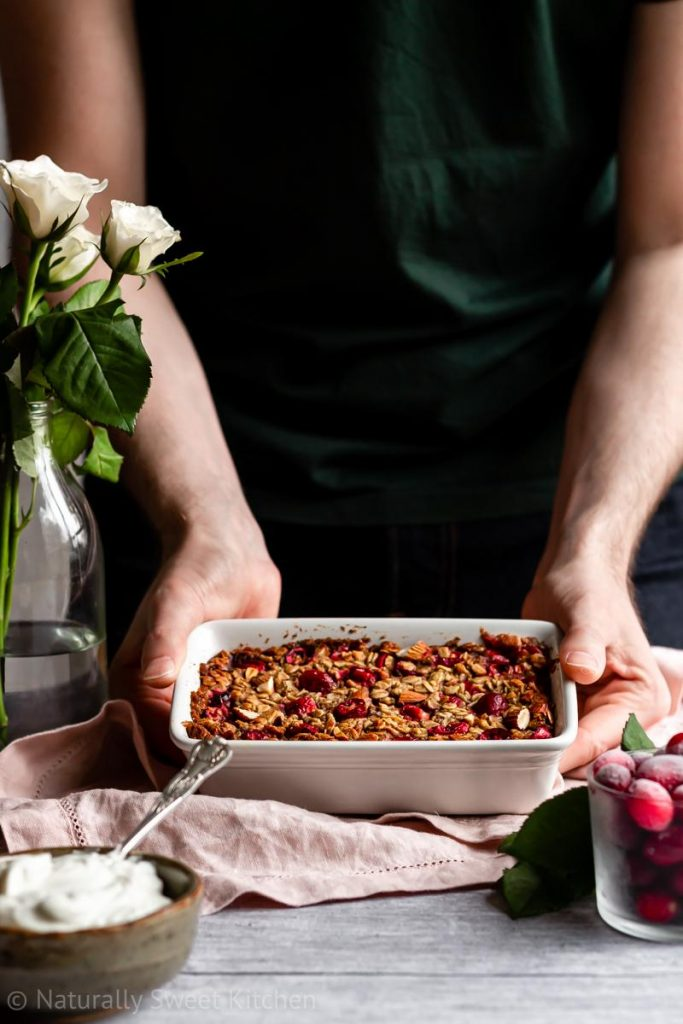 a man in a green shirt serving a dish of cranberry oat bake from a small white baking dish
