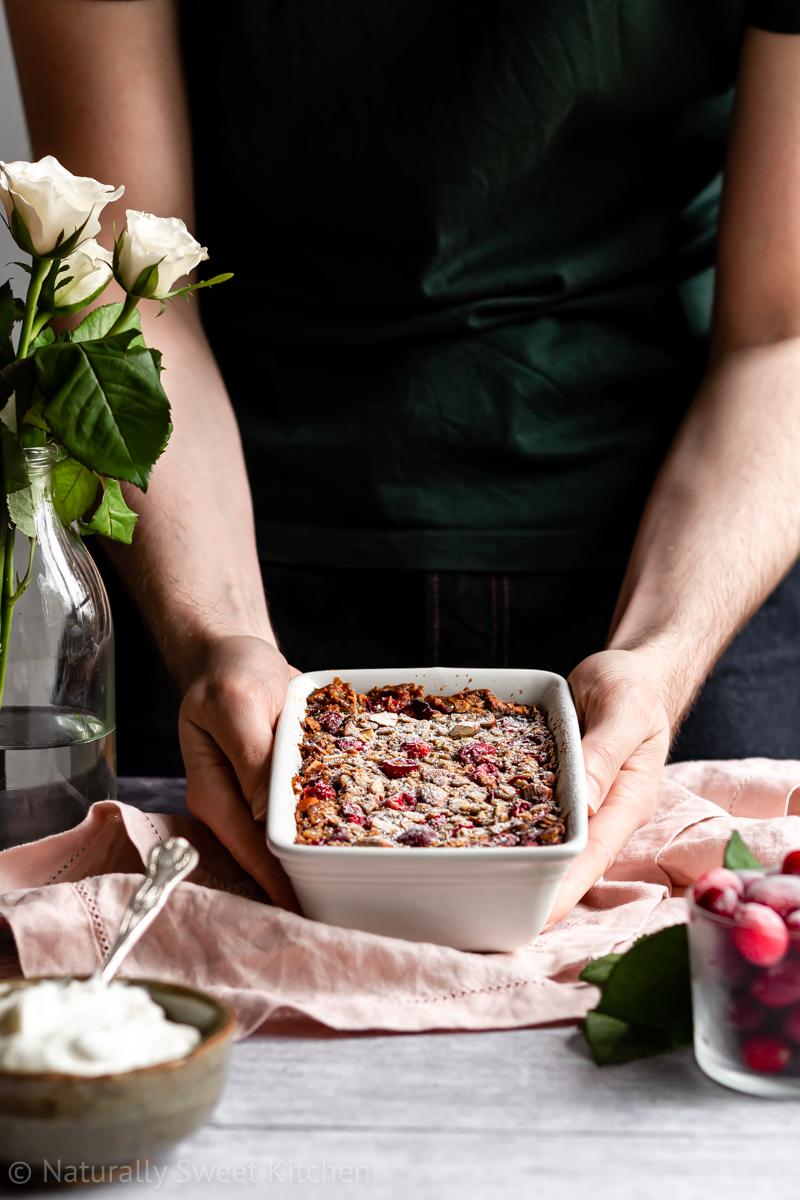 a man in a green shirt placing a dish of baked oats with cranberries on a pink linen napkin on top of a wooden table.