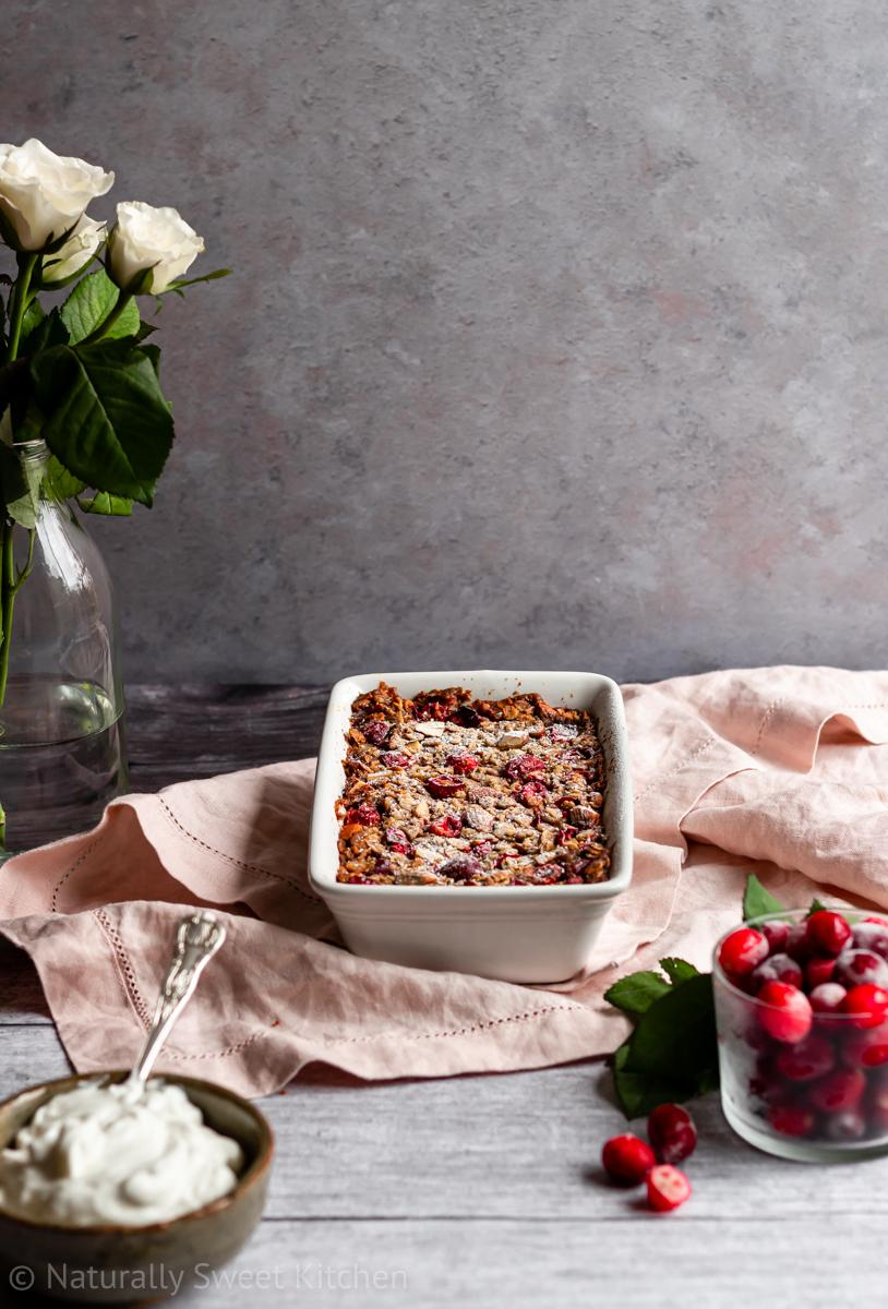 a small batch serving of cranberry baked oats on top of a pink linen napkin on a wooden table surrounded by white roses, cranberries, and a bowl of yoghurt