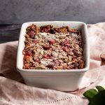 a small batch of baked oats with cranberries and almonds in a white baking dish topped with powdered sugar