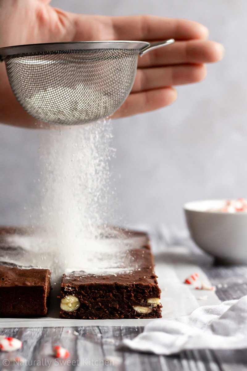 a dusting of icing sugar falls on two rows of mint chocolate brownies from a small metal sieve.