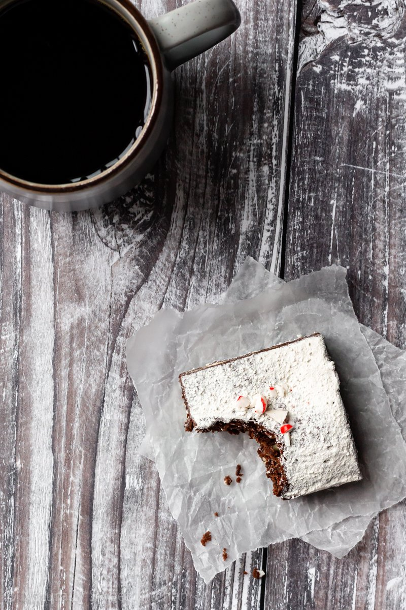 a square of chocolate mint brownie with a bite taken out of it on top of a piece of parchment paper with a mug of black coffee on the side