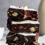 a stack of white chocolate chip studded mint chocolate brownies topped with powdered sugar and peppermint dust