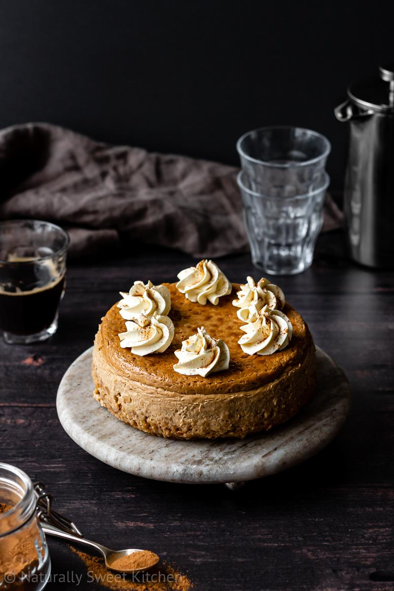 a small gingerbread cheesecake made without refined sugar on a grey brown marble serving stone topped with piped whipped cream. there is a brown linen napkin in the background as well as espresso cups and a silver carafe.
