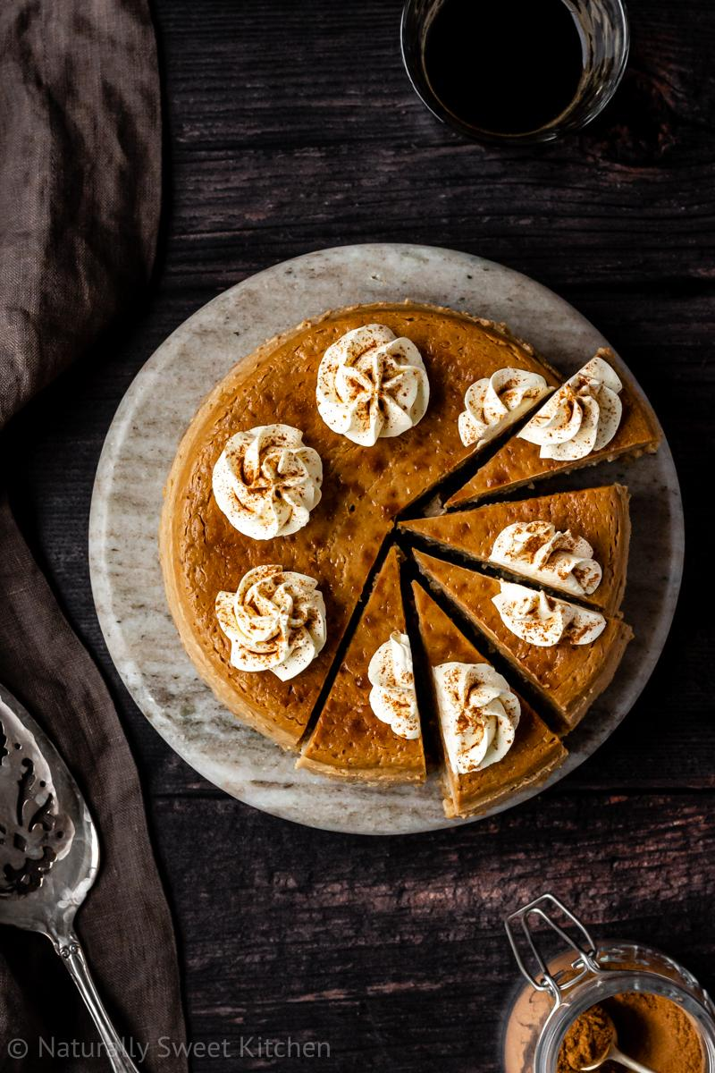 an aerial shot of a refined sugar free gingerbread cheesecake on a brownish grey serving stone with slices cut out of the right hand side