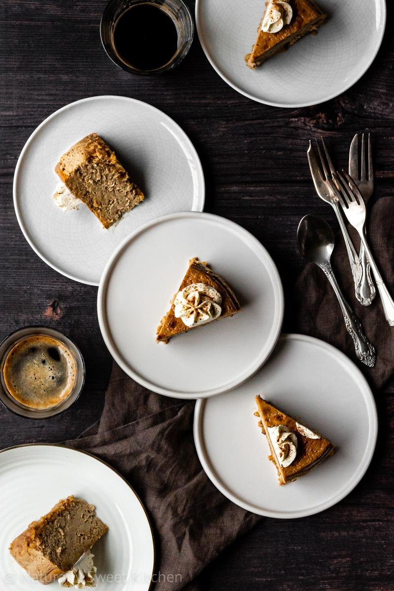 five slices of gingerbread cheesecake on white plates on a dark wooden background surrounded by coffees and silver cutlery