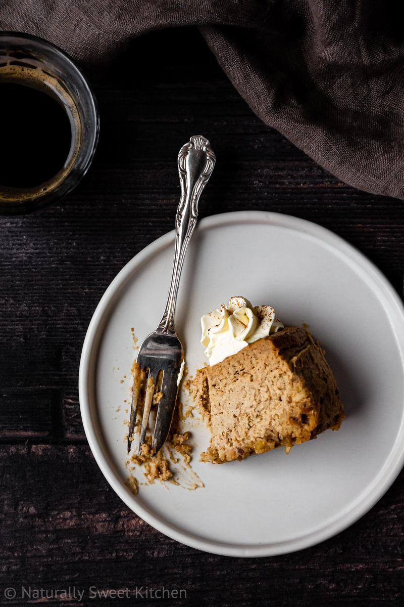 an aerial shot of a small slice of gingerbread cheesecake on a white plate with a forkful missing and a cup of espresso on the side