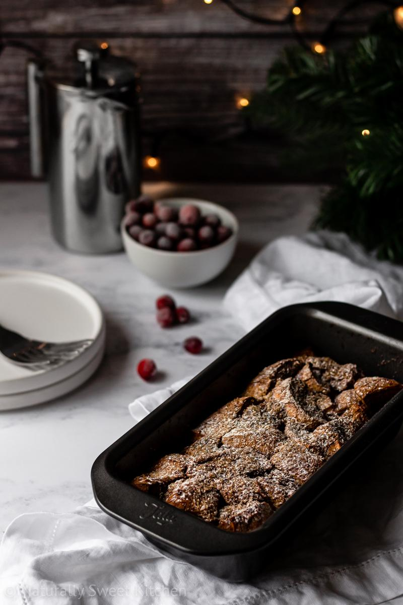 a small batch of gingerbread french toast topped with powdered sugar being served on a marble table with cranberries, coffee, and fairy lights in the background