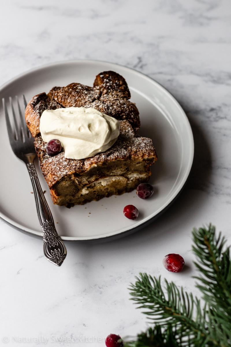 a slice of healthy gingerbread french toast on a white plate topped with frozen cranberries and whipped cream