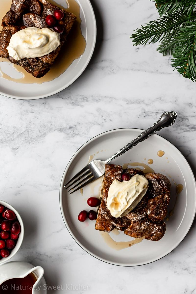 an aerial shot of two slices of refined sugar free gingerbread french toast bake topped with whipped cream, maple syrup, and cranberries on a marble background