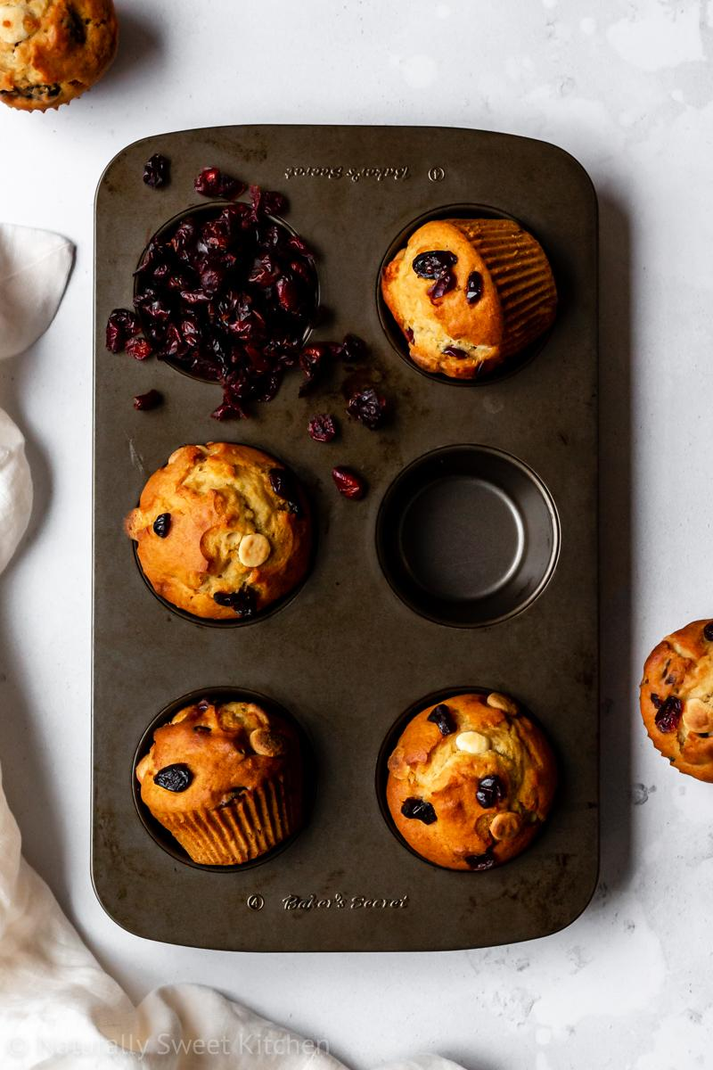 a 6-cup muffin tin is filled with four refined sugar free white chocolate cranberry muffins and surrounded by a pale tan linen and two more muffins