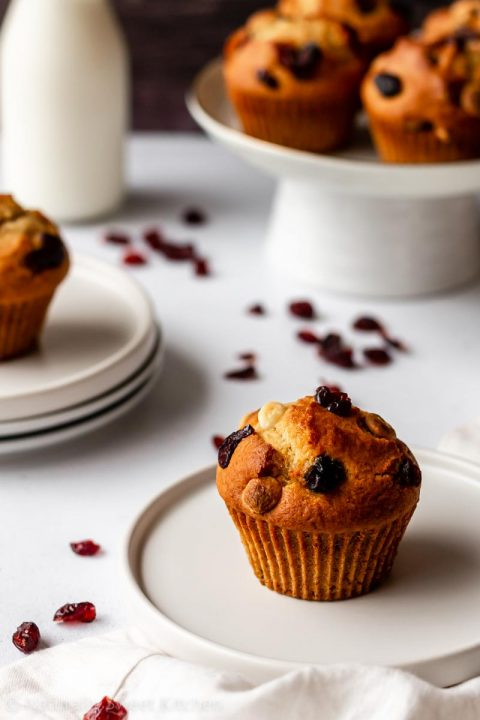 a single muffin filled with dried cranberries and white chocolate chips is sitting on a small serving plate with cranberries scattered around it and other muffins in the background