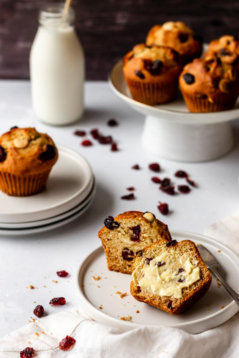 a white chocolate cranberry muffin is cut apart on a white plate with butter smeared on one half while four other muffins on a cake plate and a milk jug are standing in the background