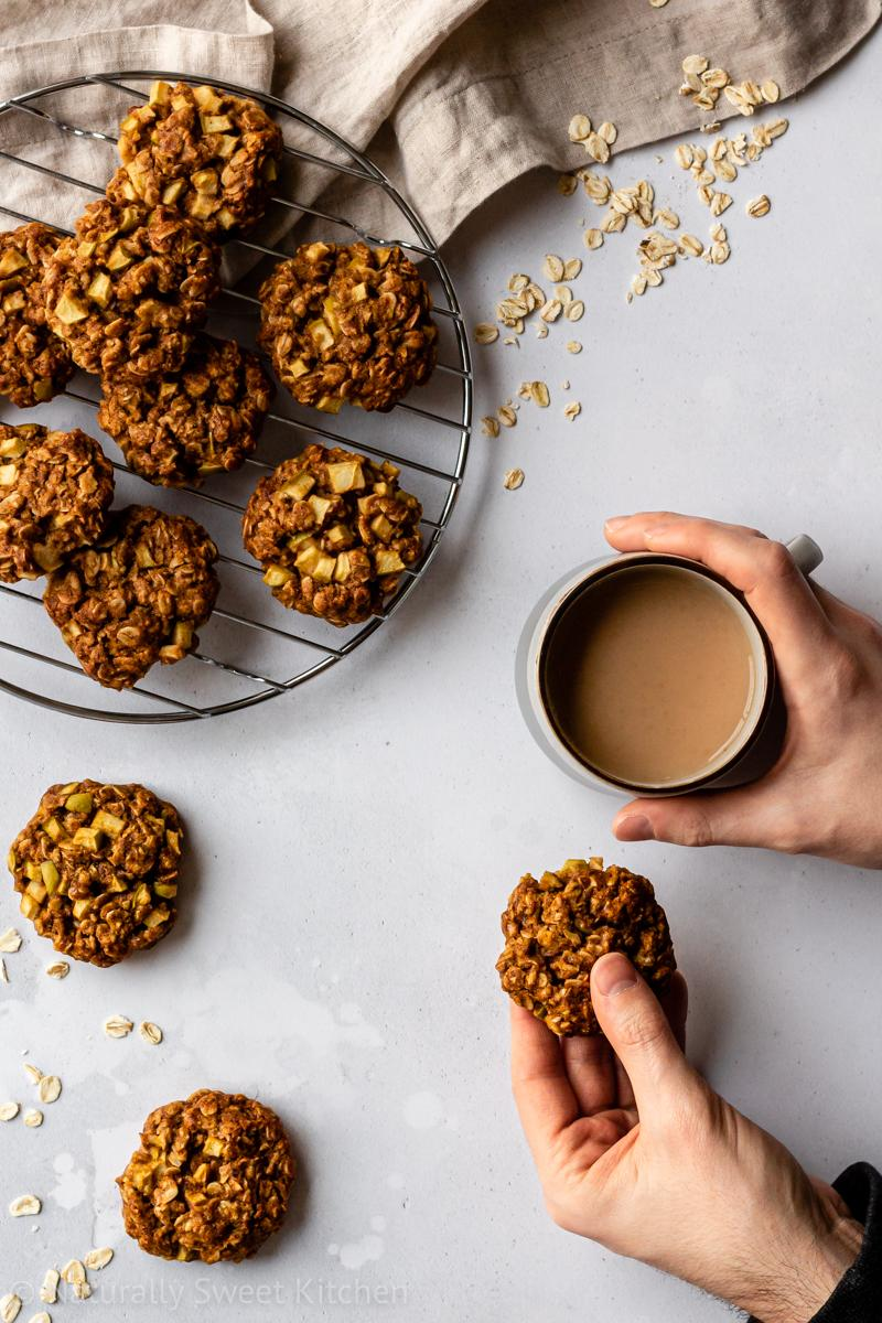 an aerial shot of healthy apple crumble cookies sitting on a round wire cooling rack – a man has taken one cookie and holds it in his hand while the opposite hand is wrapped around a mug of tea