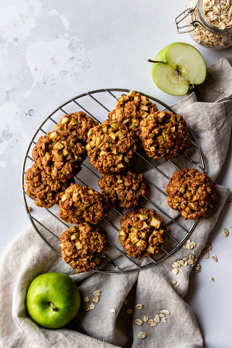 an aerial shot of a pile of healthy apple crumble cookies on a round wire cooling rack with a brown linen napkin underneath, surrounded by green apples