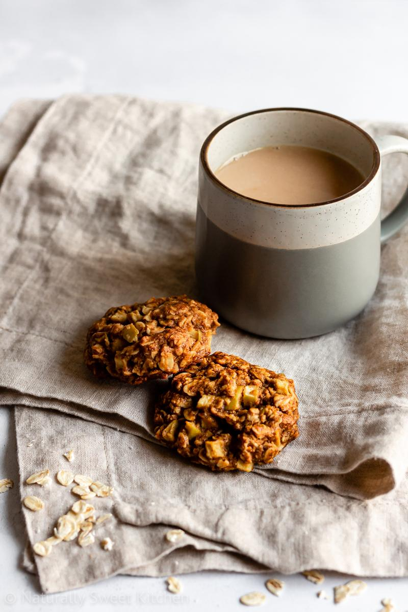 healthy cookies with apples and oats on a brown linen napkin sat next a mug of tea