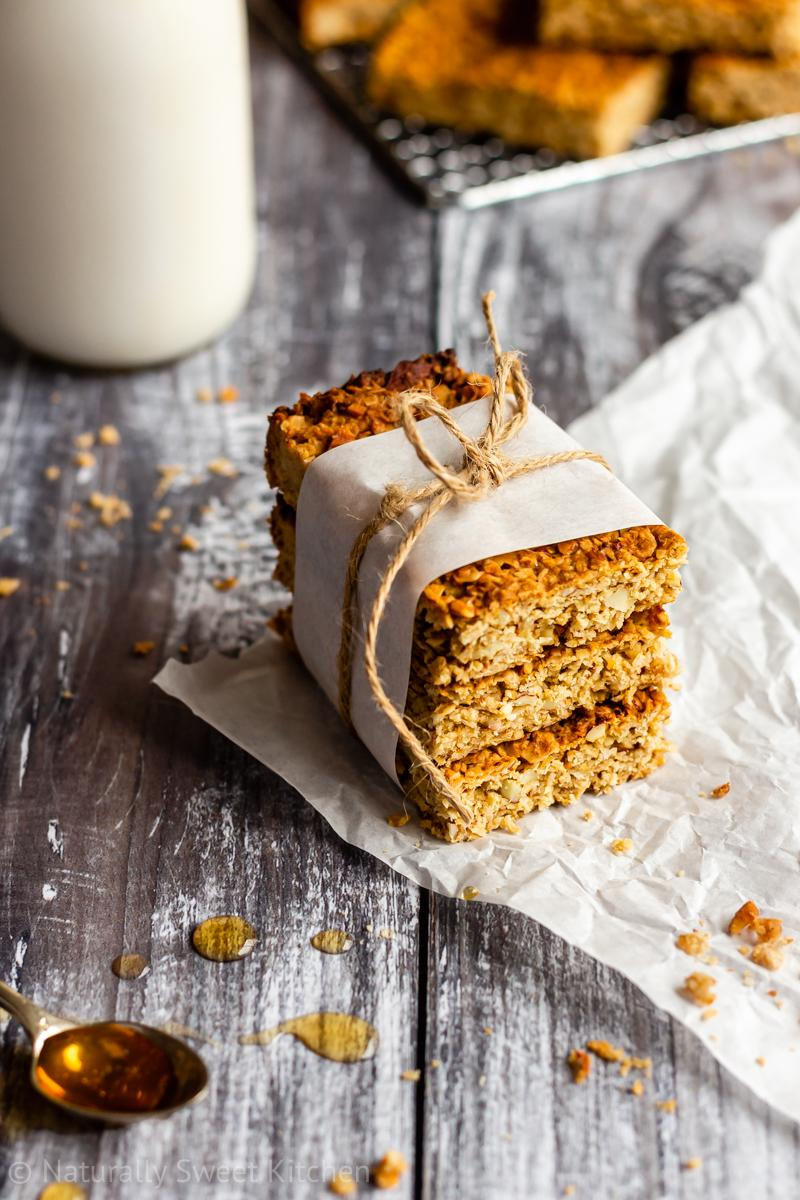 Three honey flapjacks with almonds made from an easy recipe are stacked and packaged up in white paper and brown twine. They are on a grey wooden table and surrounded with honey drips, crumbs, and a jug of milk