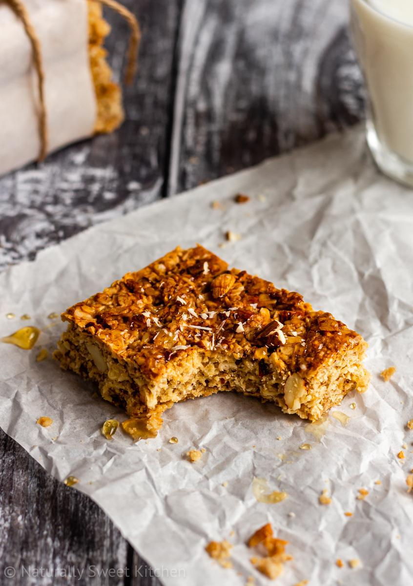 A bite has been removed from the flapjack on the grey wooden table and is topped with a drizzle of honey and crushed almonds.
