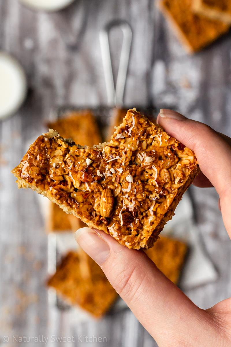 a hand holds a slice of an easy flapjack recipe topped with honey drizzle and crushed almonds with a bite removed from the corner