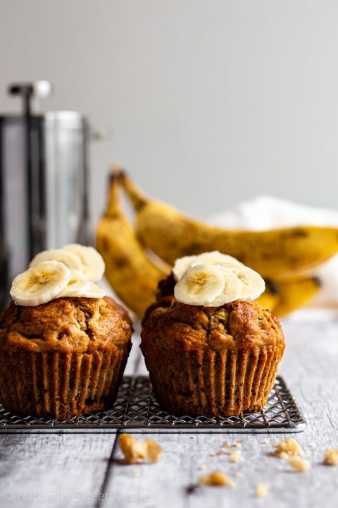 a serving of healthy banana muffins on a metal cooling rack topped with banana slices with broken nuts in the foreground