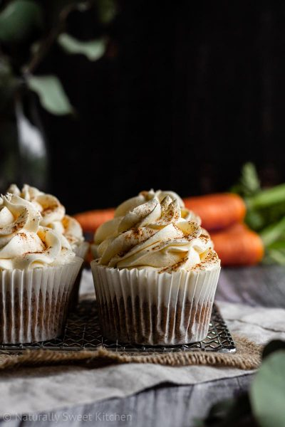 a close up of 4 refined sugar free carrot cake cupcakes on a silver wire rack with carrots and greenery in the background