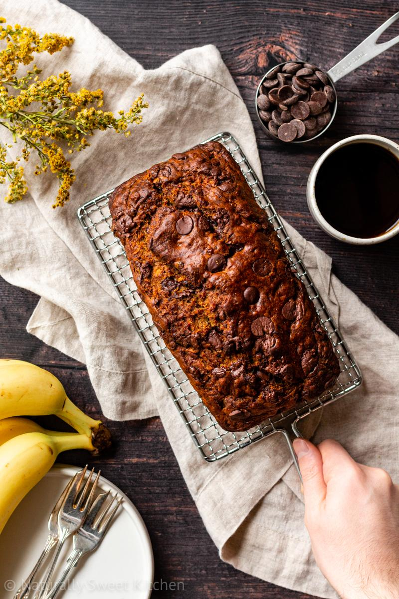 a hand serves a loaf of refined sugar free chocolate chip banana bread on a wire rack