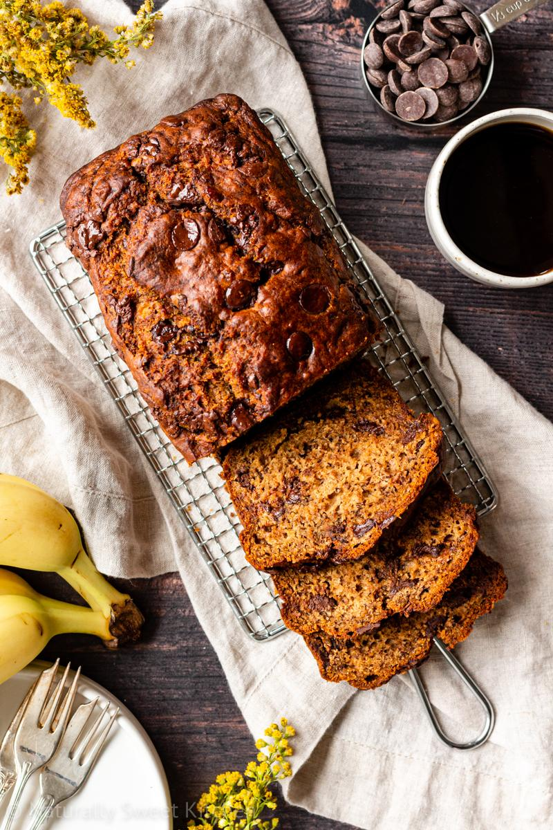 an aerial shot of sliced chocolate chip banana bread sitting on a wire rack on top of a wooden table with a mug of coffee and cup of chocolate chips in the corner of the image