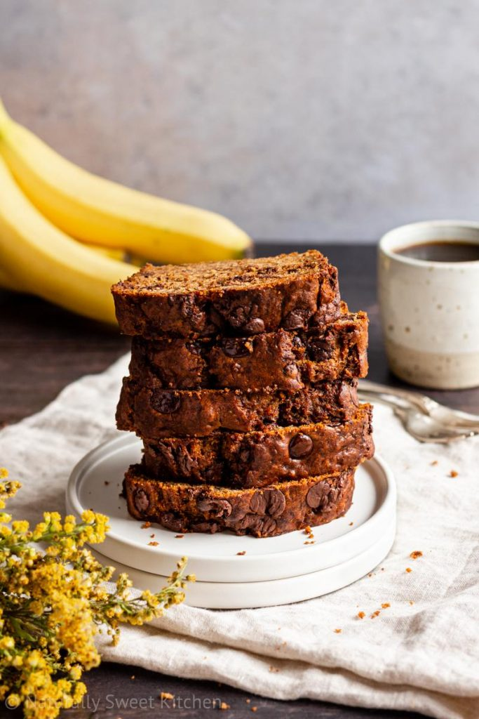a stack of banana bread filled with chocolate chips on a white plate with a mug of coffee and bananas in the background