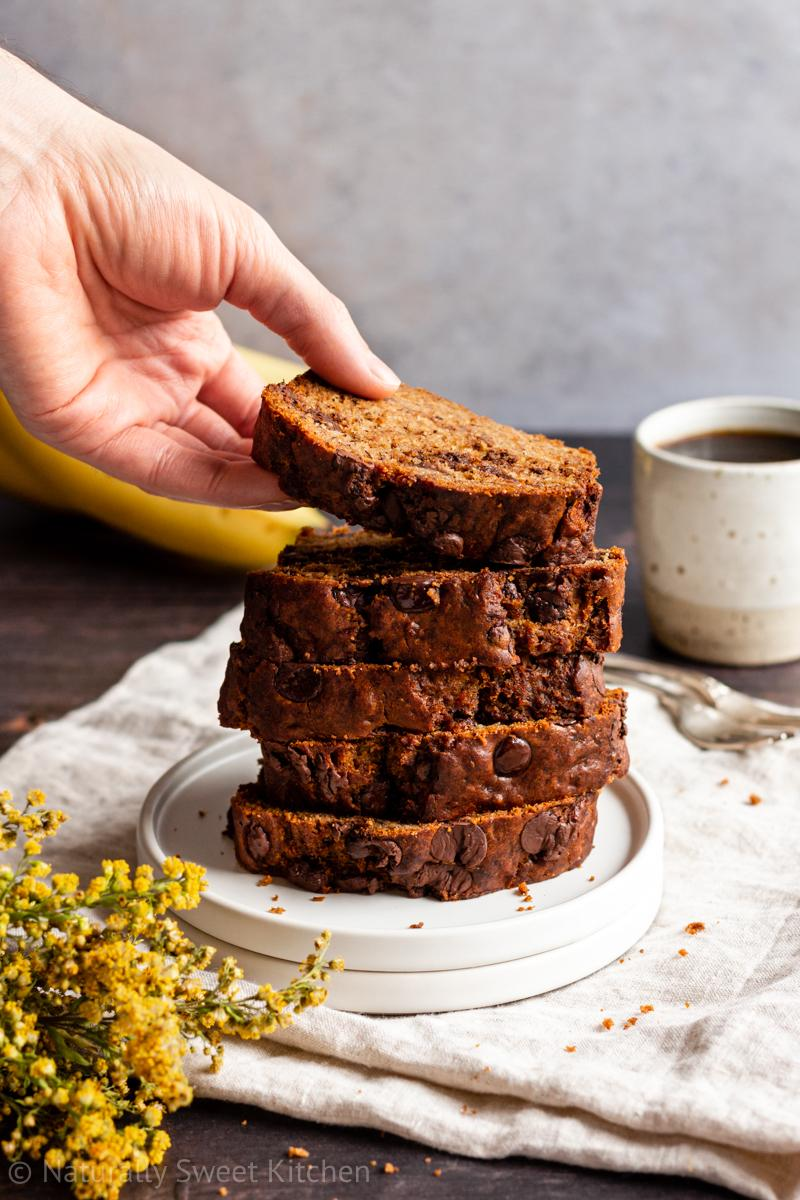 a hand reaches to take a slice of refined sugar free banana bread from a large stack on a plate