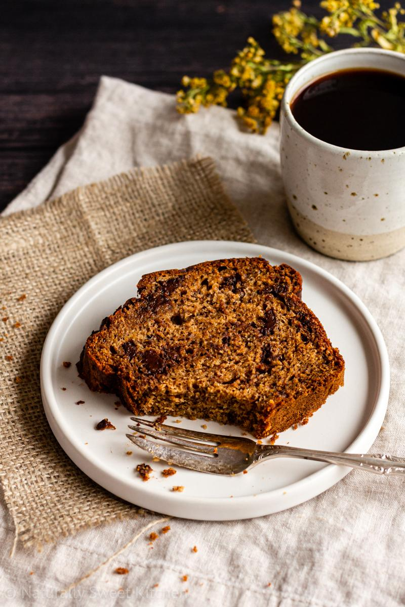 A slice of refined sugar free chocolate chip banana bread on a white plate with a piece taken out of it with a cake fork and a mug of coffee on the side
