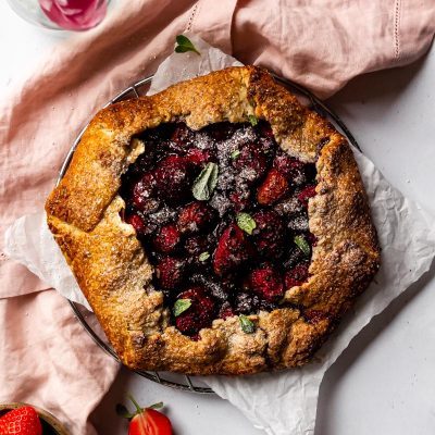 a chocolate strawberry galette topped with fresh mint sitting on top of a wire cooling rack surrounded by strawberries, pink tulips and a pink linen napkin