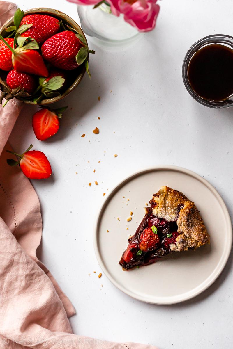 a slice of rustic chocolate and strawberry pie on a white plate topped with fresh mint and surrounded with fresh strawberries, pink tulips, and a glass of espresso