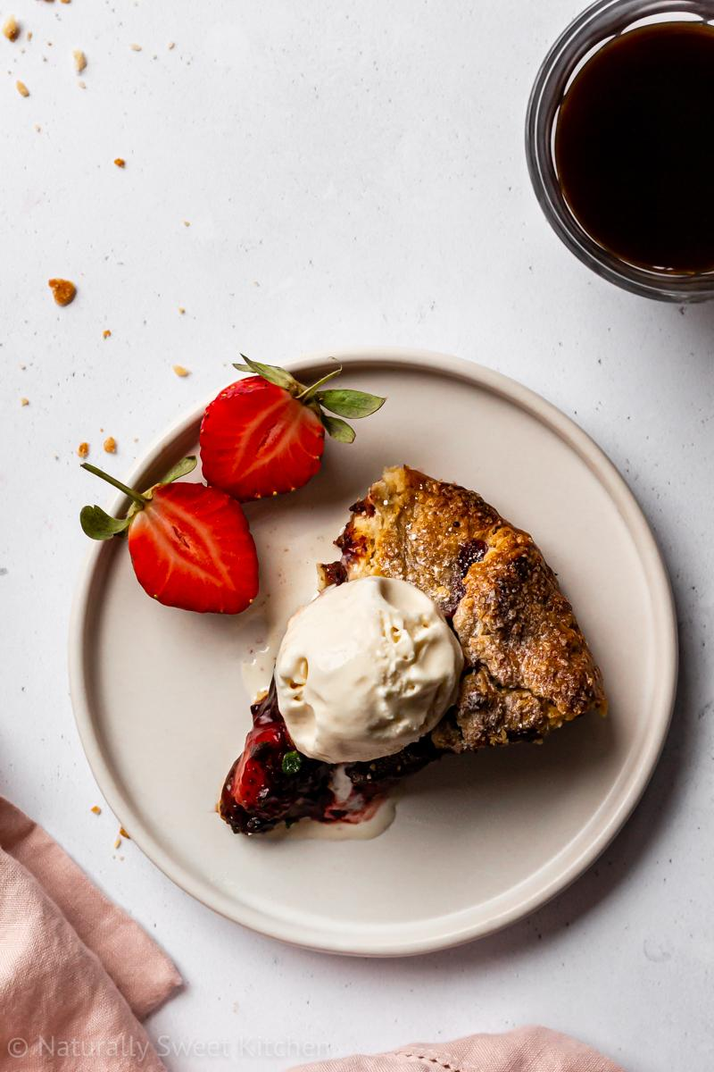 A slice of chocolate strawberry galette on a white plate, topped with vanilla ice cream and fresh strawberries with a cup of espresso on the side