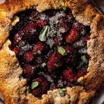 a close up shot of a chocolate strawberry galette topped with fresh mint and a dusting of powdered sugar