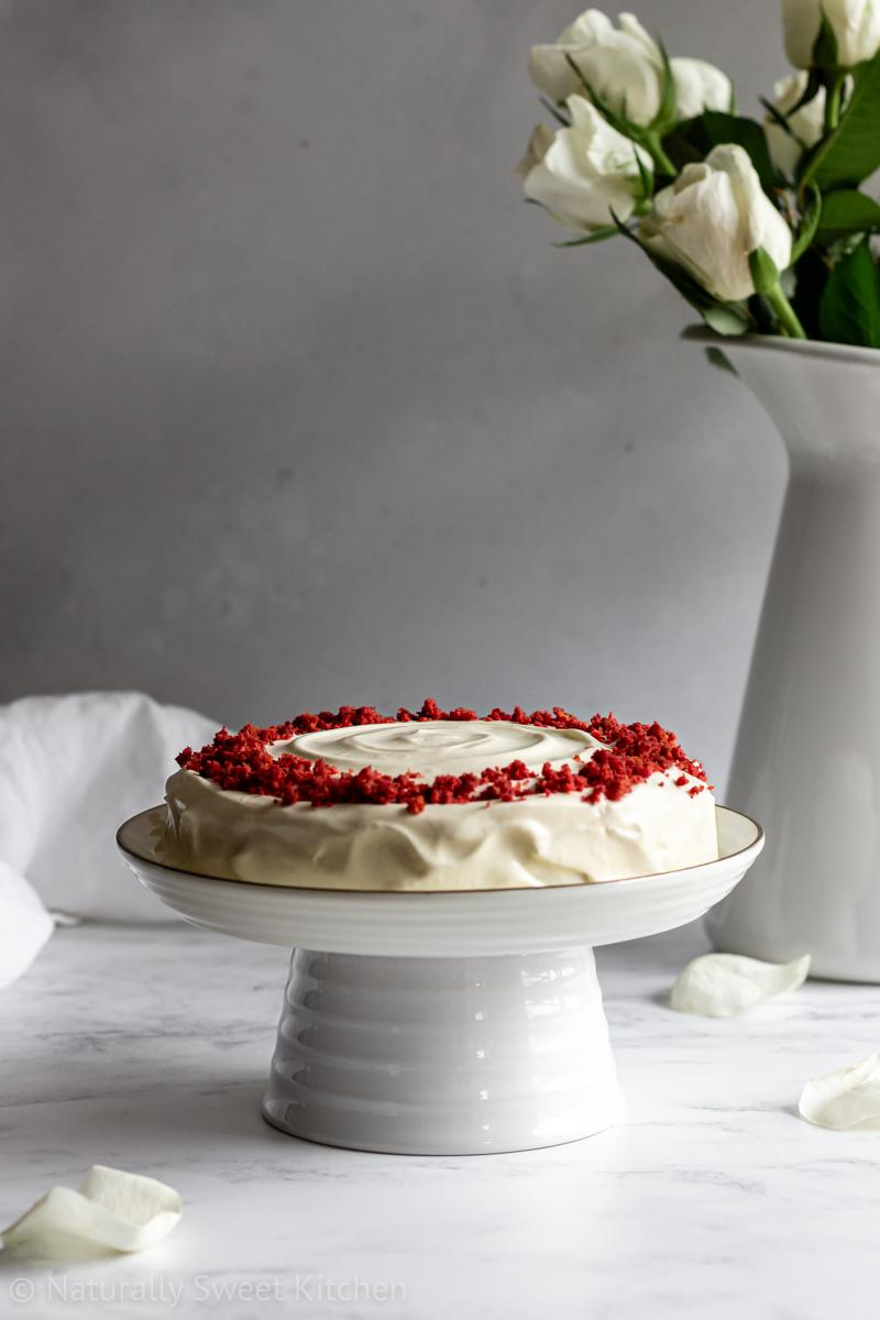 a natural red velvet cake decorated with beetroot dyed crumbles on a mini cake stand in front of a vase of white roses.