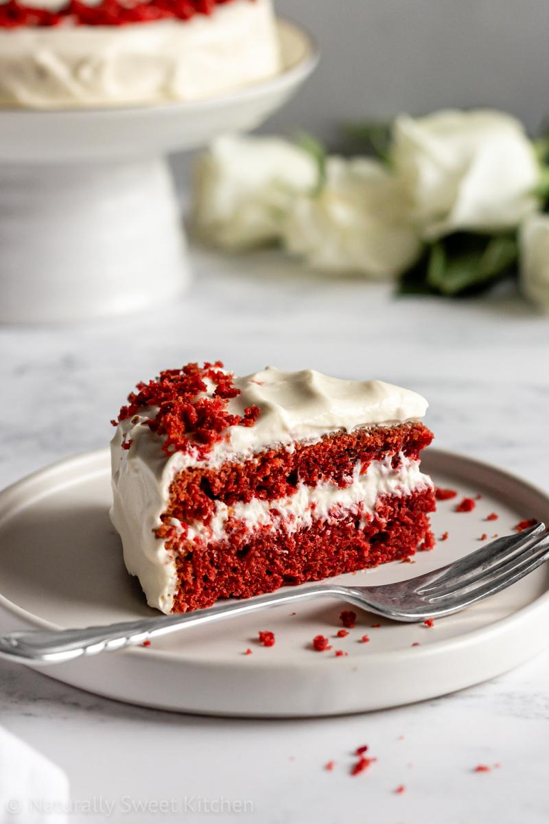 a slice of naturally sweet red velvet cake coloured with beetroot powder on a white plate with a silver antique fork