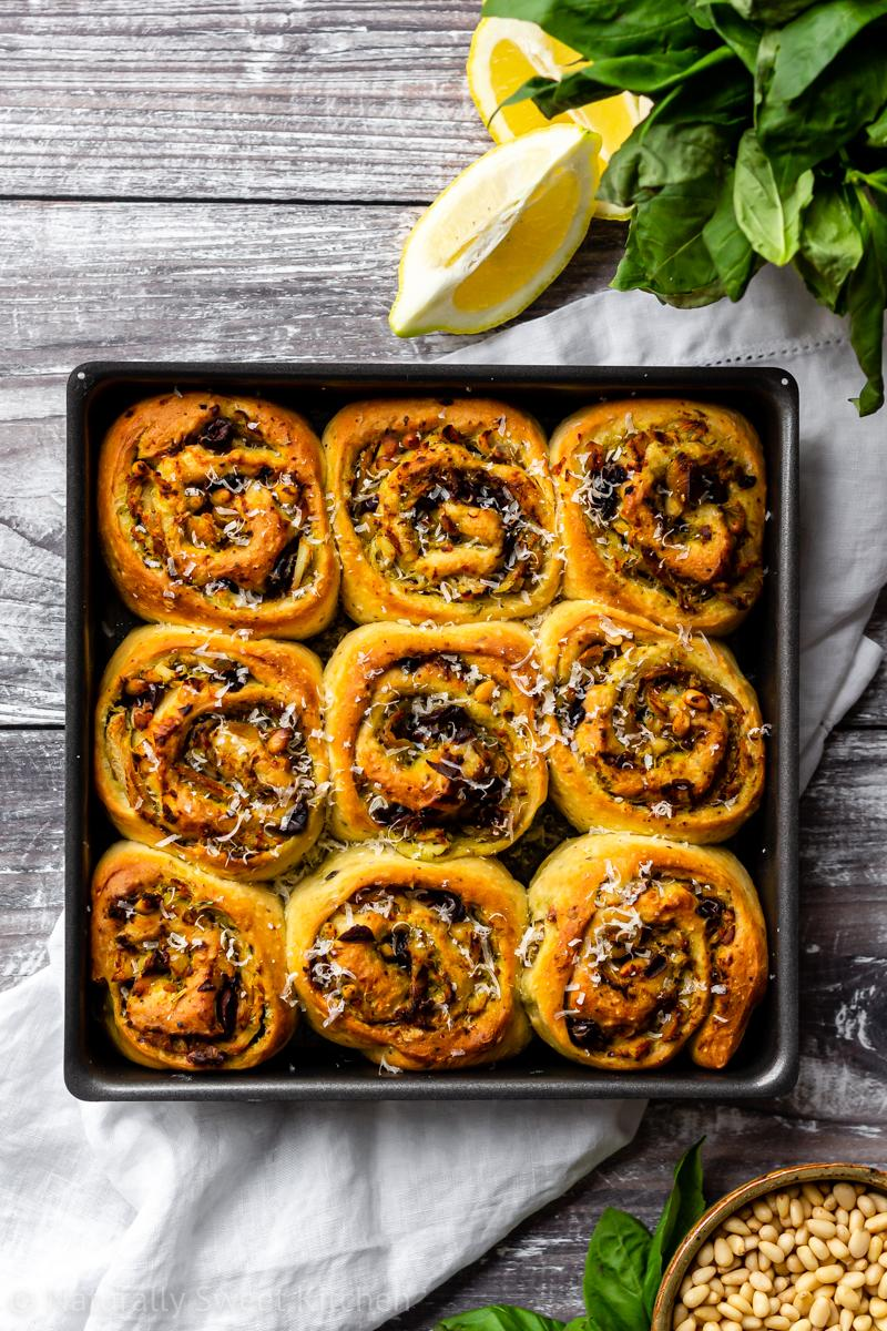an aerial shot of 9 pesto chicken rolls in a square baking tray on top of a white linen napkin surrounded with basil, lemon wedges and pine nuts