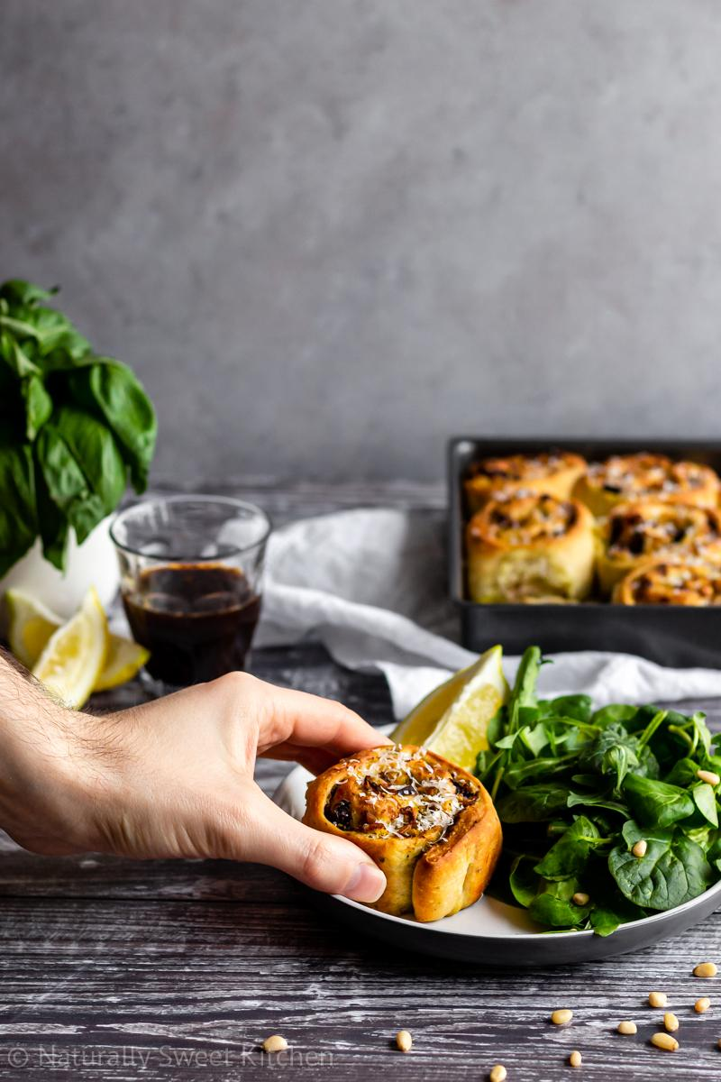 a hand places a pesto chicken roll onto a plate next to a side green salad. there is a pot of basil and espresso cup in the background along with the tray of rolls