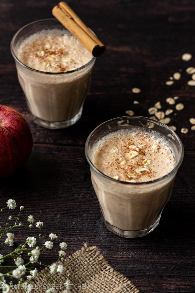 two glasses of apple smoothie on a wooden table with red apples and rolled oats surrounding them