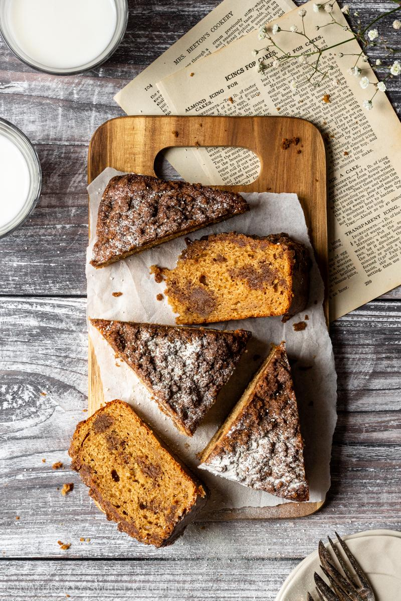 a wooden serving board with slices of refined sugar free coffee loaf cake with cookery book pages and glasses of milk surrounding it
