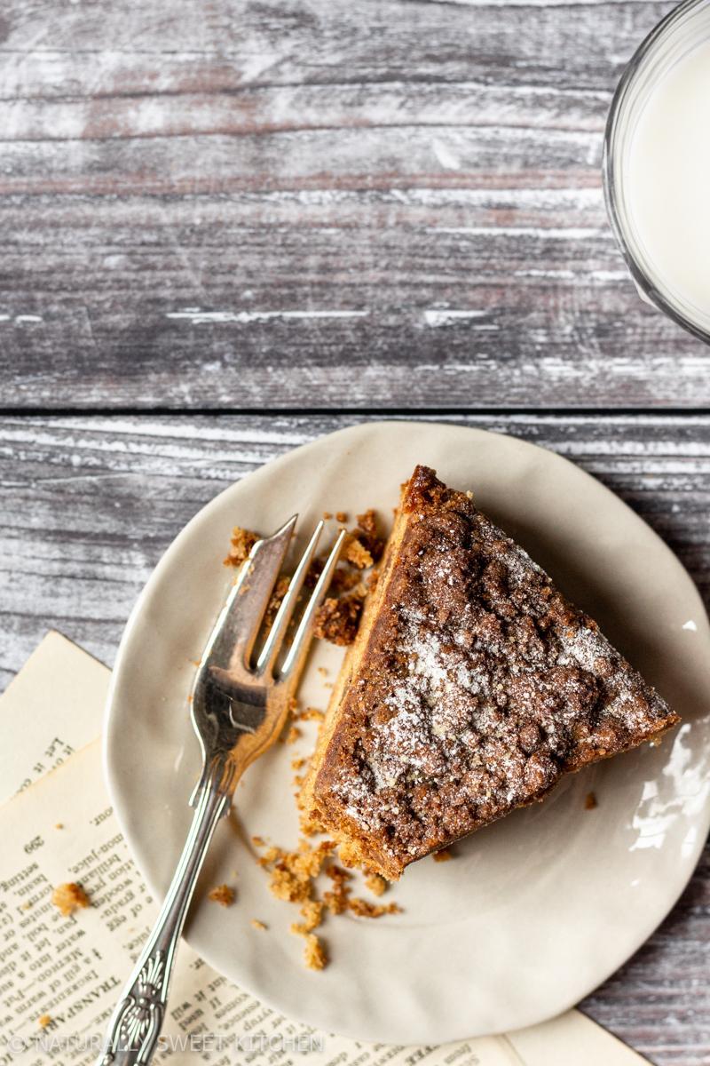 an aerial shot of a slice of cinnamon coffee loaf cake with a bite taken out of it and crumbs surrounding the cake fork
