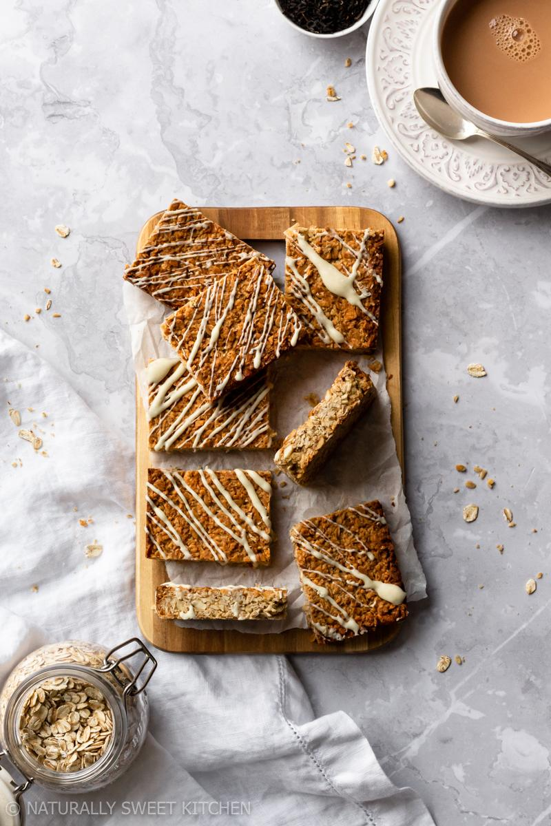 an aerial view of a platter of earl grey tea latte flapjacks on a grey marble table with a cup of tea and a jar of oats surrounding it