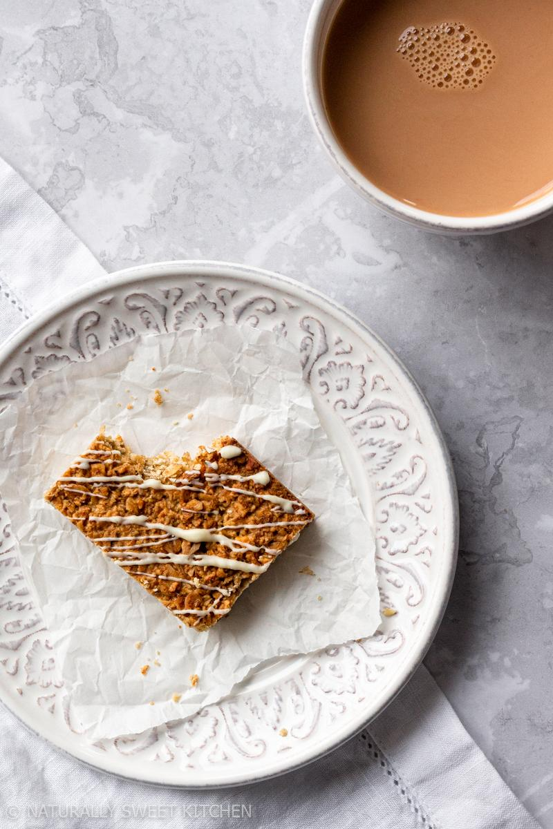 a single london fog flapjack sits on a white plate with a bite taken out of it next to a mug of tea