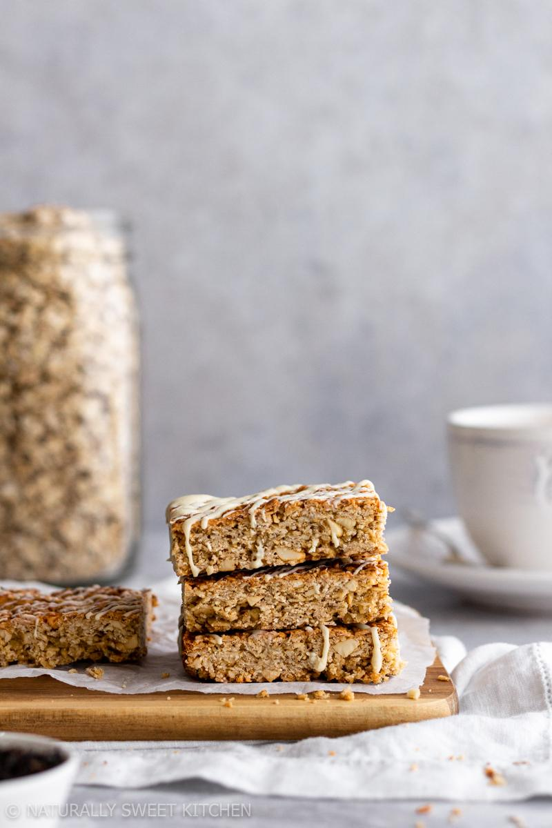 a stack of earl grey tea latte flapjacks on a wooden board with a cup of tea and jar of rolled oats in the background