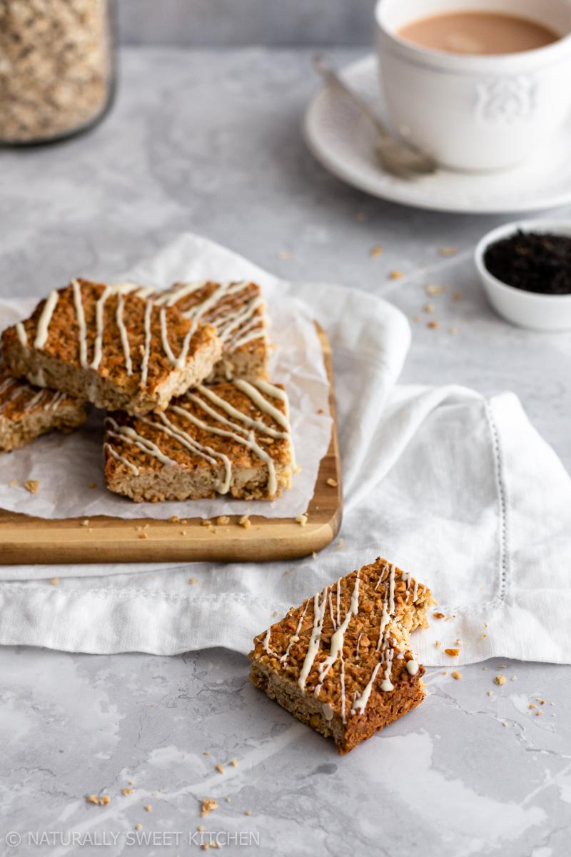 A pile of london fog flapjacks drizzled in white chocolate sit on a wooden board with one flapjack in front with a bite taken out of it