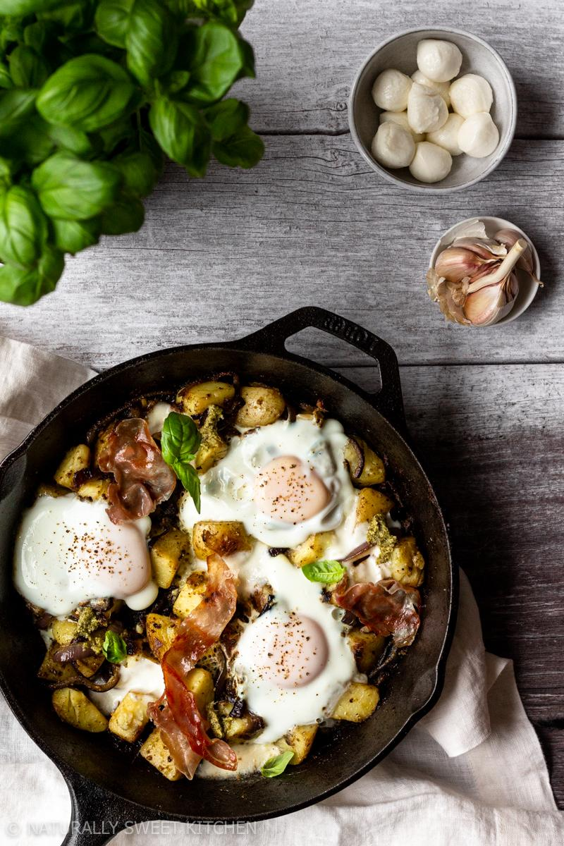 a skillet of pesto breakfast hash topped with steamed eggs on a wooden table surrounded by a basil plant, a bowl of bocconcini and garlic cloves
