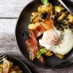 two servings of pesto breakfast hash on matte black plates set on a white and grey wooden table