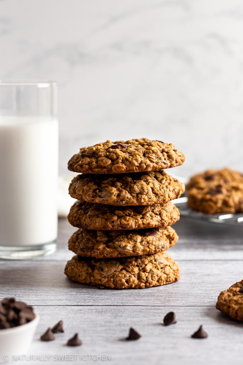 a stack of golden oatmeal chocolate chip cookies made without brown sugar on a wooden table with a glass of milk in the background