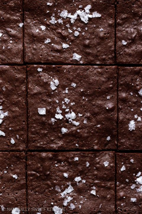 a close up texture shot of some refined sugar free brownies topped with sprinkles of sea salt