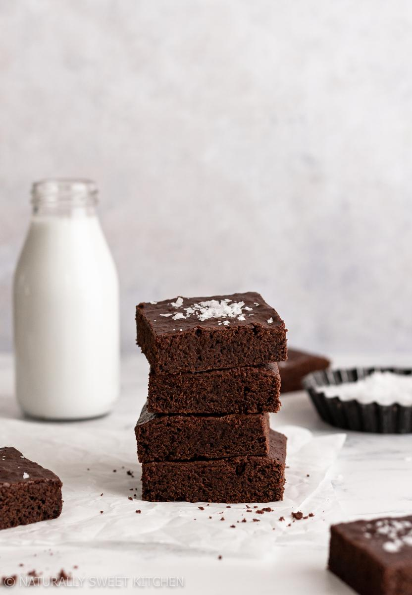 a stack of four refined sugar free brownies surrounded by additional slices, sea salt, and a bottle of milk